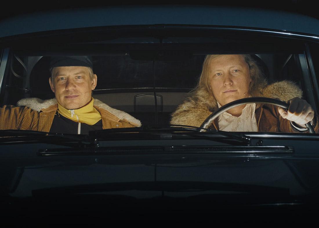 Kaksi miestä istuu vanhassa autossa illan hämärässä, elokuvallinen markkinointi Oulun teatterin näytelmästä.