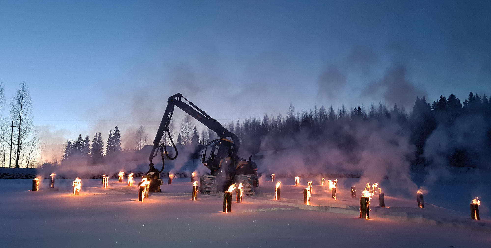 Ponsse Scorpion -metsäkone jätkänkynttilöiden keskellä iltahämärässä.