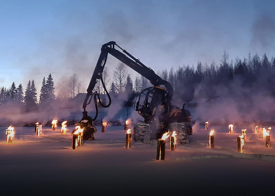 Tuotelanseeraus: Ponsse Scorpion metsäkone jätkänkynttilöiden keskellä iltahämärässä.